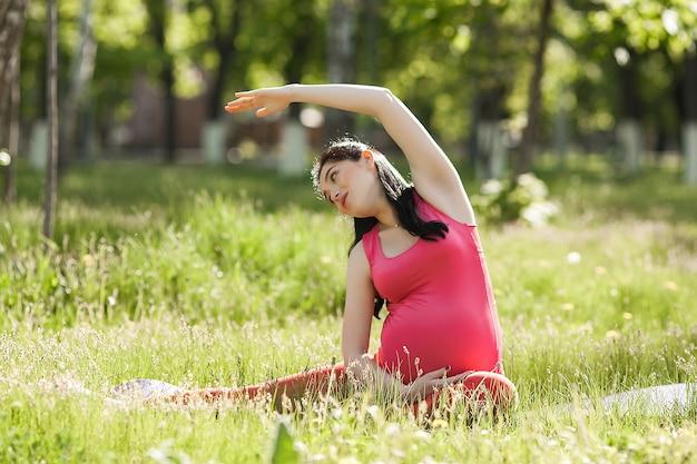 Jovem grávida fazendo exercícios de ioga ao ar livre no parque.