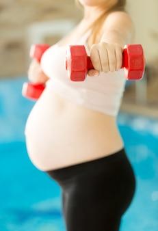 Jovem grávida levantando halteres na academia