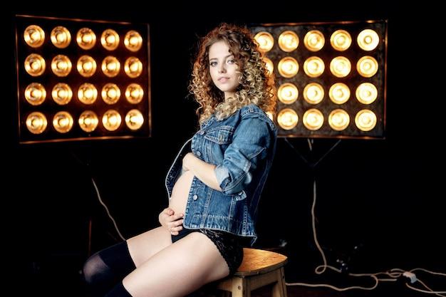 Jovem grávida linda loira modelo mulher com jaqueta jeans em estúdio, sentada na cadeira