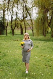 Jovem grávida loira com vestido cinza, grávida na primavera em uma caminhada, conceito de maternidade