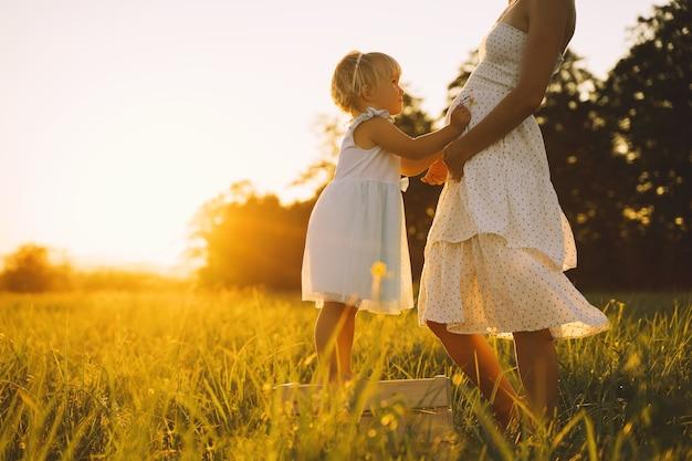 Jovem grávida mãe e filha em um vestido na natureza ao ar livre mulher grávida e criança no prado