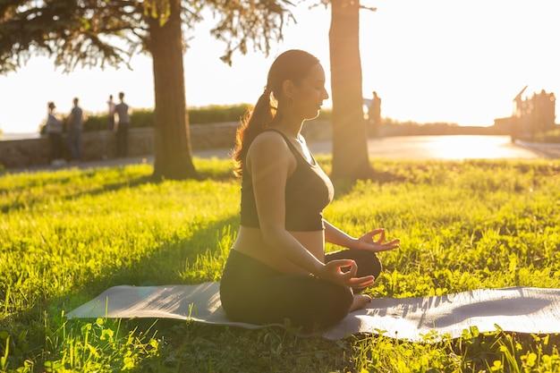 Jovem grávida meditando na natureza, pratica ioga. cuidados com a saúde e a gravidez.