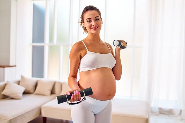 Jovem grávida no sportswear fazendo exercícios com halteres na sala de estar. esportes e estilo de vida saudável durante a gravidez.