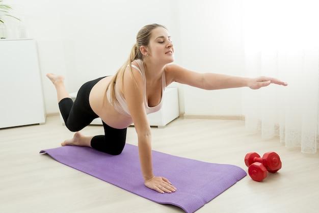 Jovem grávida se exercitando e se alongando na esteira de ginástica em casa