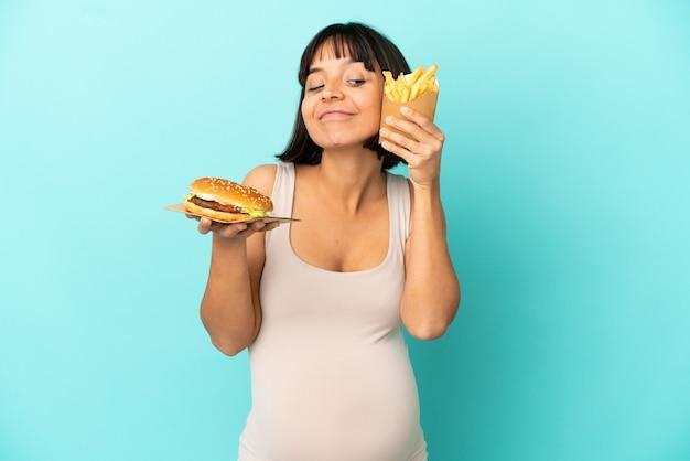 Jovem grávida segurando hambúrguer e batatas fritas sobre fundo azul isolado