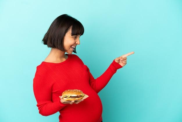 Jovem grávida segurando um hambúrguer sobre um fundo isolado, apontando o dedo para o lado e apresentando um produto