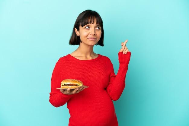 Jovem grávida segurando um hambúrguer sobre um fundo isolado, cruzando os dedos e desejando o melhor