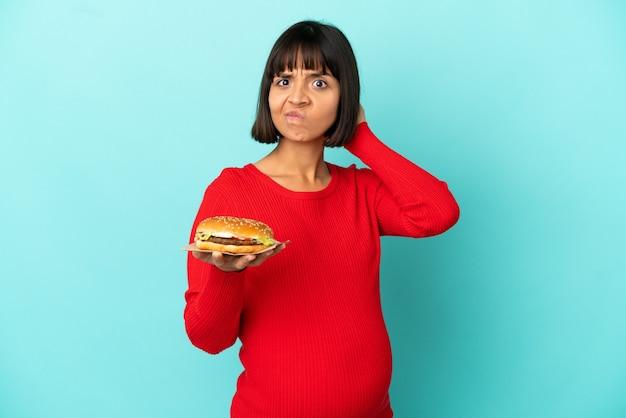 Jovem grávida segurando um hambúrguer sobre um fundo isolado e tendo dúvidas