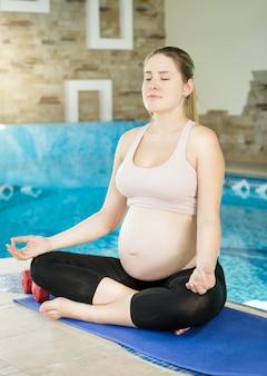 Jovem grávida sentada com as pernas cruzadas no tapete de fitness