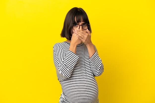 Jovem grávida sobre fundo amarelo isolado, cobrindo a boca com as mãos