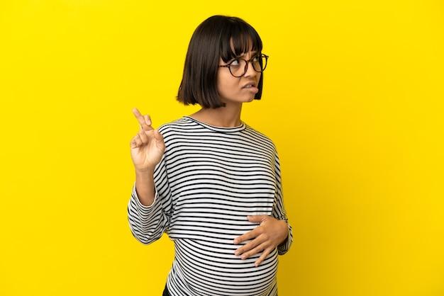 Jovem grávida sobre fundo amarelo isolado com dedos se cruzando e desejando o melhor
