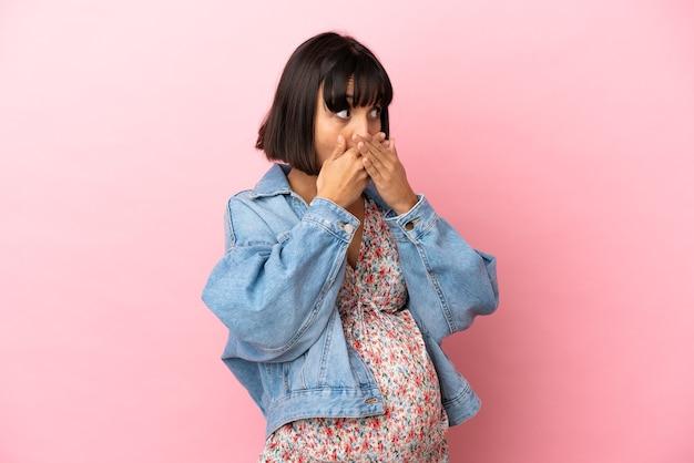 Jovem grávida sobre fundo rosa isolado, cobrindo a boca e olhando para o lado