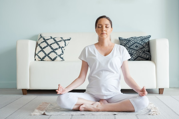 Jovem grávida sorridente de branco medita sentada em posição de ioga no chão em casa, closeup