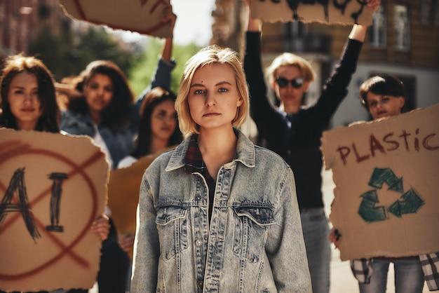 Jovem greve climática em trajes casuais protestando com grupo de ativistas ao ar livre na estrada
