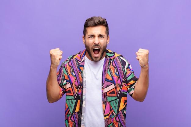Jovem gritando agressivamente com uma expressão de raiva ou com os punhos cerrados celebrando o sucesso