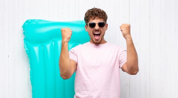 Jovem gritando agressivamente com uma expressão de raiva ou com os punhos cerrados celebrando o sucesso.