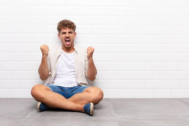 Jovem gritando agressivamente com uma expressão de raiva ou com os punhos cerrados