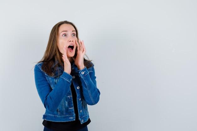 Jovem gritando ou anunciando algo na blusa, jaqueta e olhando animada, vista frontal.