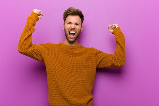 Jovem gritando triunfante, parecendo vencedor animado, feliz e surpreso, comemorando