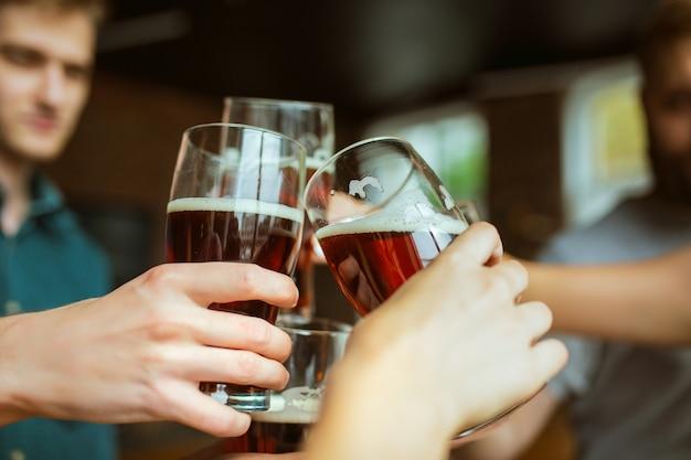 Jovem grupo de amigos a tilintar de garrafas de cerveja, a divertir-se e a festejar juntos.