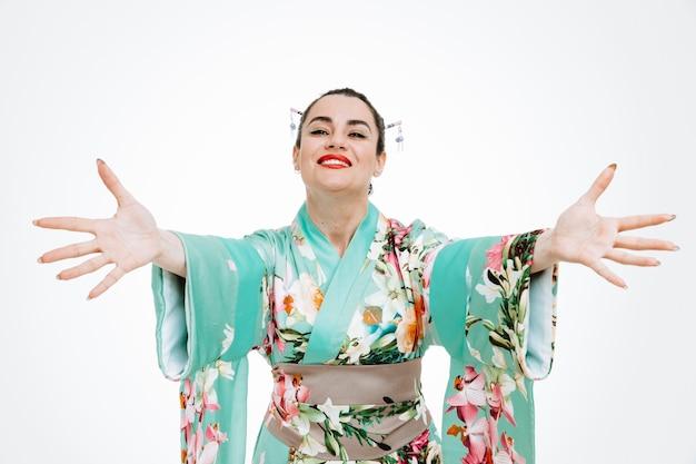 Jovem gueixa em quimono japonês tradicional olhando para a frente sorrindo alegremente, fazendo gesto de boas-vindas, abrindo as mãos em pé sobre a parede branca