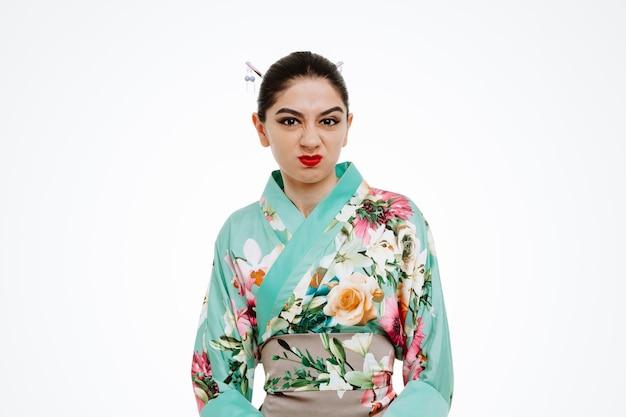 Jovem gueixa em quimono japonês tradicional olhando para frente com cara de raiva fazendo uma boca irônica em pé sobre a parede branca