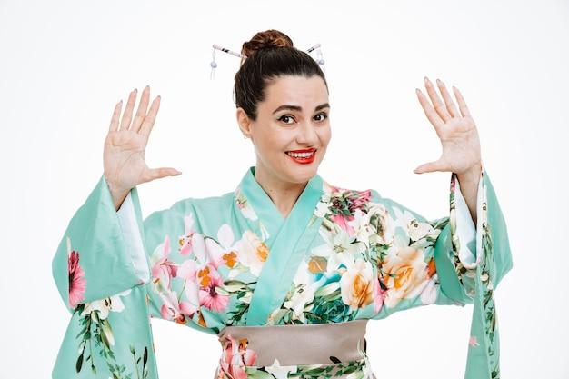 Jovem gueixa em quimono japonês tradicional olhando para frente sendo surpreendida e feliz levantando as mãos, mostrando o número dez em pé sobre uma parede branca