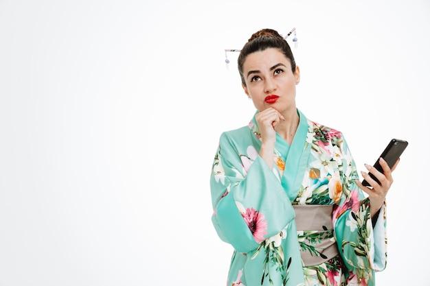 Jovem gueixa em quimono japonês tradicional segurando um smartphone, olhando para cima com uma expressão pensativa em pé sobre uma parede branca