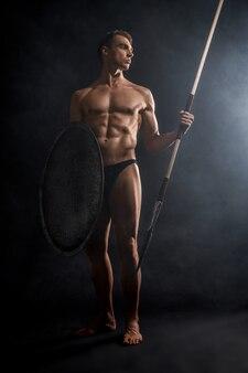 Jovem guerreiro segurando lança e escudo.