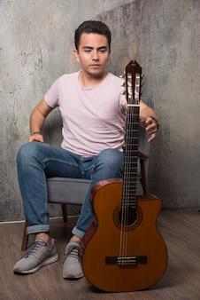 Jovem guitarrista segurando a guitarra no fundo de mármore