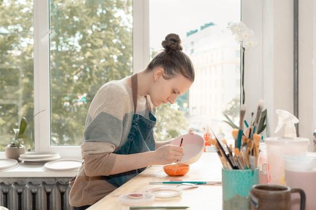 Jovem habilidosa de avental sentada à mesa e desenhando na tigela de cerâmica na oficina de cerâmica