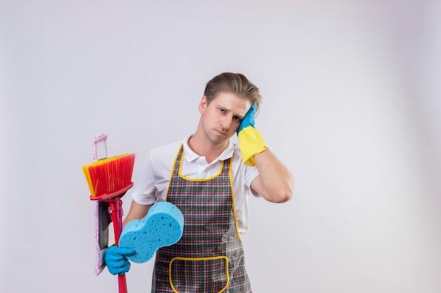 Jovem hansdome usando avental e luvas de borracha segurando esfregões e esponja cansado e com excesso de trabalho