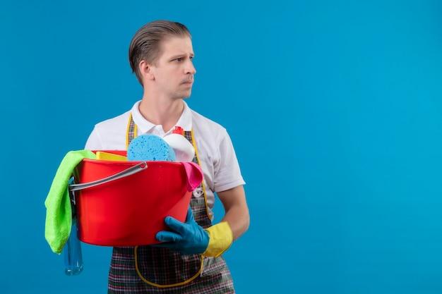 Jovem hansdome usando avental e luvas de borracha segurando um balde com ferramentas de limpeza