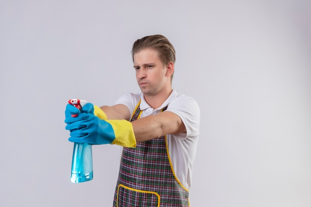 Jovem hansdome usando avental e luvas de borracha segurando um spray de limpeza como uma arma com uma cara séria em pé sobre uma parede branca
