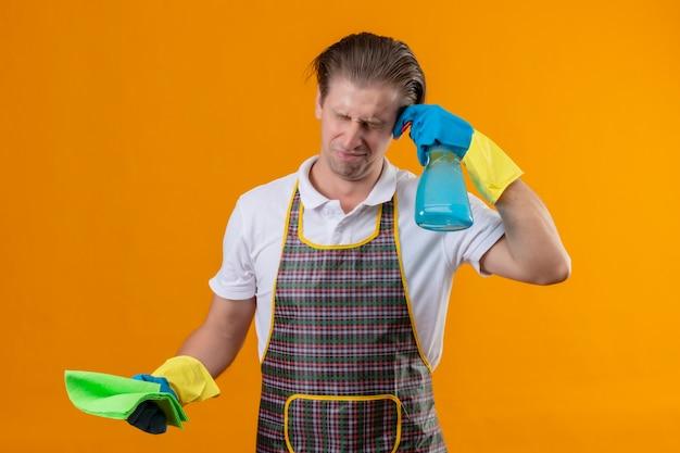 Jovem hansdome usando avental e luvas de borracha segurando um spray de limpeza e um tapete