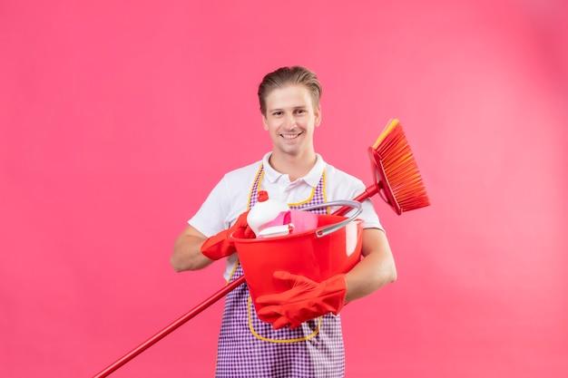 Jovem hansdome vestindo avental segurando balde com ferramentas de limpeza e esfregão sorrindo confiante em pé sobre a parede rosa