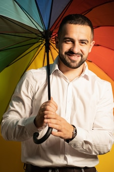 Jovem heterossexual com um guarda-chuva arco-íris nas costas