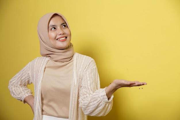 Jovem hijab exibindo espaço de cópia em uma parede amarela