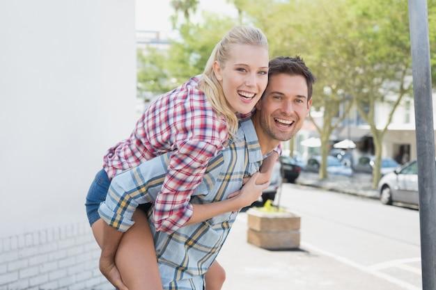 Jovem hip homem dando a namorada loira um piggy back