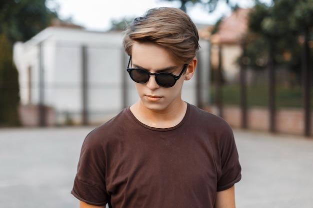 Jovem hippie americano urbano em óculos de sol em t-shirt da moda com penteado em uma quadra de basquete moderna ao ar livre.