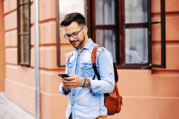 Jovem hippie atraente em pé ao ar livre e usando um telefone inteligente