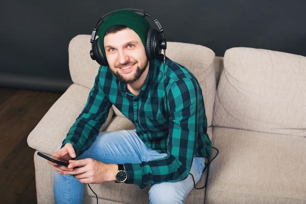 Jovem hippie barbudo sentado em um sofá em casa, ouvindo música em fones de ouvido