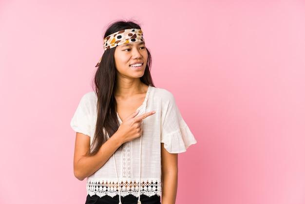 Jovem hippie chinesa isolada sorrindo e apontando de lado, mostrando algo no espaço em branco.