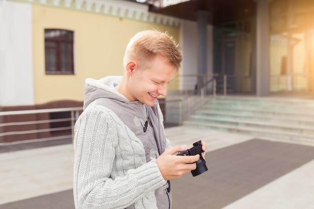 Jovem hippie com uma câmera na cidade, conceito de viagens