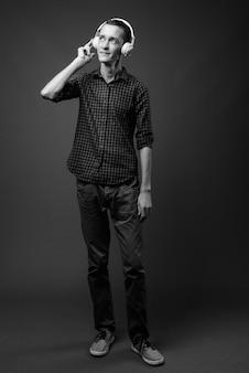 Jovem hippie contra uma parede cinza em preto e branco