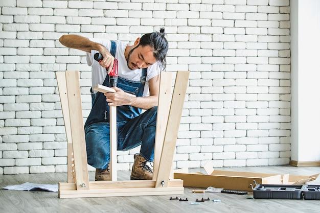 Jovem hippie de avental trabalhando como faz-tudo, montando mesa de madeira com equipamentos, conceito de bricolage em casa e self-service.