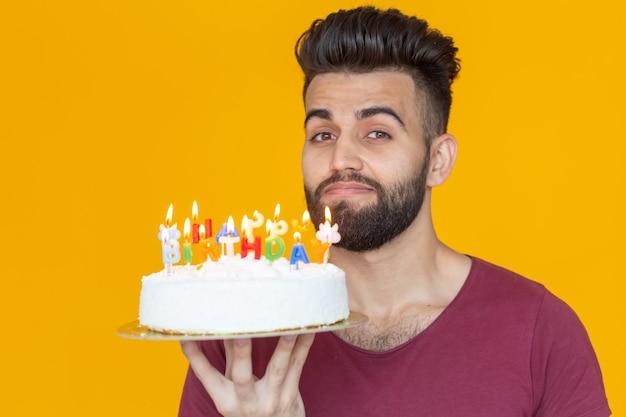 Jovem hippie masculino com barba segurando um bolo com a inscrição parabéns!