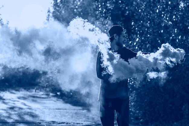 Jovem hippie masculino feliz, pule e exploda a bomba de fumaça laranja em um dia de verão no parque verde.