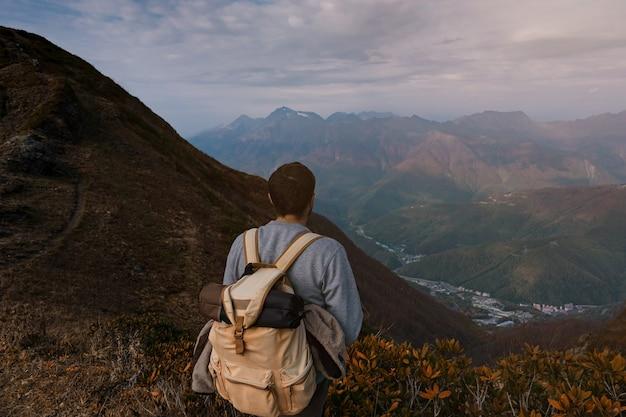 Jovem hippie masculino nas montanhas no outono. conceito de destino de viagens de descoberta. turista no fundo de pedras altas. esporte e conceito de vida ativa.