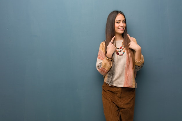 Jovem hippie mulher sorri, apontando a boca